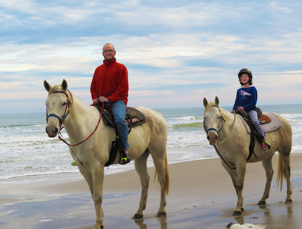 father and daughter on horses on the beach