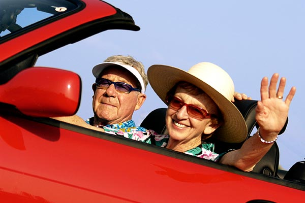 older couple in red car waving